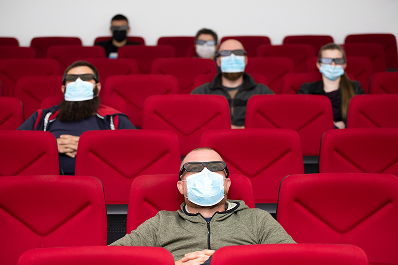 People in masks spread out in theater